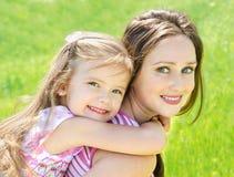 微笑的美丽的少妇和她的一点daughte画象  免版税库存照片