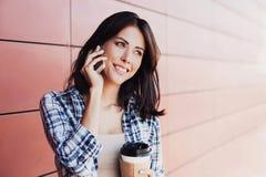 微笑的美丽的年轻女人谈话在智能手机在城市 库存图片