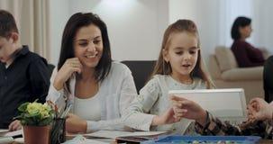 微笑的美丽的成熟的妇女和非常吸引人她的三个的孩子,他们一起有了不起的时光在家庭作业以后 股票录像