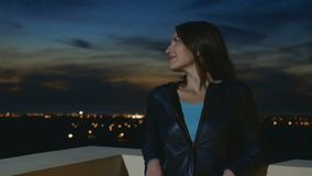 微笑的美丽的浅黑肤色的男人站立在屋顶晚上背景 股票视频
