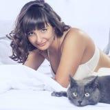 微笑的美丽的深色的女孩在她的床和猫上 库存照片
