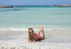 微笑的美丽的白肤金发的女孩在海滩说谎 库存照片
