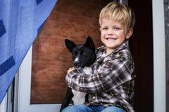 微笑的美丽的白肤金发的孩子和他的狗 男孩和basenji 免版税库存图片