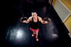 微笑的美丽的肌肉妇女为锻炼做准备在健身房 免版税库存照片