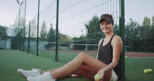 微笑的美丽的sportiv妇女,在使用与在camer前面的网球的网球比赛前 影视素材