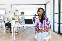 微笑的美国黑人的办公室工作者画象offfice的与她的同事 免版税库存图片