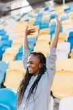 微笑的美国黑人的少年的特写镜头画象 女孩为队欢呼,当坐时 免版税库存照片