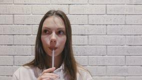 微笑的美女喝着从管的一个饮料 股票录像