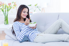 微笑的美好深色放松在长沙发和吃沙拉 库存图片