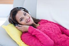 微笑的美好深色放松在长沙发和听的音乐 免版税库存照片