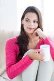 微笑的美好深色放松在长沙发和拿着杯子 库存照片