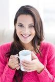 微笑的美好深色放松在长沙发和拿着杯子 库存图片