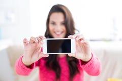 微笑的美好深色放松在长沙发和采取selfie 免版税库存图片