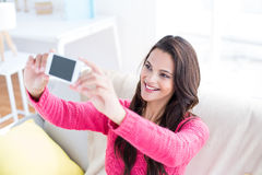 微笑的美好深色放松在长沙发和采取selfie 库存照片