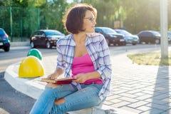 微笑的美好深色放松户外和阅读书 免版税图库摄影