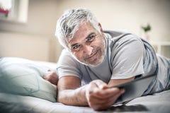 微笑的老人在床上 库存图片