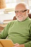 微笑的老人纵向有书的 库存图片