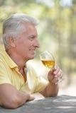 微笑的老人饮用的酒 库存照片