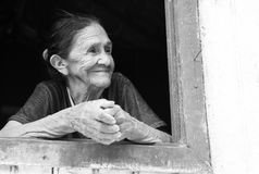 微笑的老妇人在窗口里 免版税图库摄影