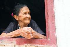 微笑的老妇人在窗口里 免版税库存照片