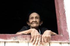 微笑的老妇人在窗口里 库存图片