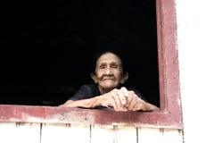 微笑的老妇人在窗口里 免版税库存图片
