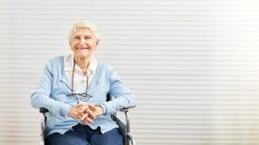 微笑的老妇人在轮椅坐在养老院 免版税图库摄影