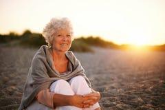 微笑的老妇人坐海滩 库存图片