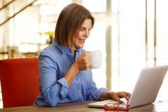 微笑的老妇人饮用的咖啡和看膝上型计算机 库存图片