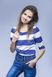 微笑的肉欲的深色的女孩自然画象有摆在时髦牛仔裤的长的头发的 库存图片
