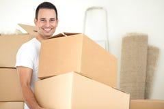 微笑的英俊的人运载的包裹 免版税图库摄影