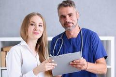微笑的英俊的医生与患者沟通 库存照片
