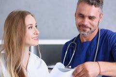 微笑的英俊的医生与患者沟通 免版税图库摄影