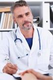 微笑的英俊的成熟医生与患者沟通 免版税库存图片