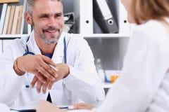微笑的英俊的成熟医生与患者沟通 免版税库存照片