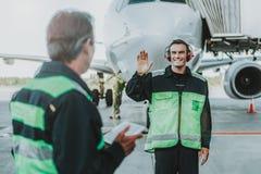 微笑的英俊的雇员在红色对技工的耳机挥动的手上 库存照片