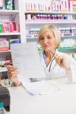 微笑的药剂师想法的和读的处方 免版税图库摄影