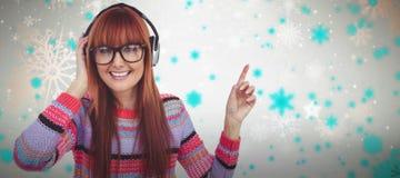 微笑的行家妇女听的音乐的综合图象与耳机的 免版税库存图片