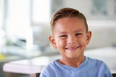 微笑的西班牙男孩首肩画象在家 免版税图库摄影