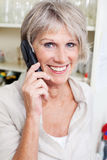微笑的资深夫人谈话在电话 免版税库存照片