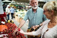微笑的资深夫妇买的菜和在merket 库存图片