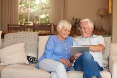 微笑的资深夫妇内容一起在他们的客厅 库存图片