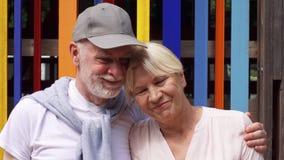 微笑的资深夫妇站立反对色的墙壁背景 无忧无虑的旅游家庭享受假期 股票录像