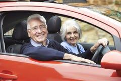 微笑的资深夫妇画象为在汽车的驱动 免版税库存照片