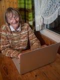 微笑的资深妇女使用一台膝上型计算机 图库摄影