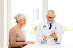 微笑的资深妇女和医生有片剂个人计算机的 免版税图库摄影