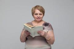 微笑的资深妇女阅读书画象  库存图片