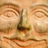 微笑的赤土陶器面孔 库存照片