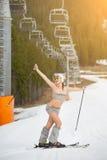 微笑的赤裸滑雪者全长画象  愉快的妇女获得在多雪的倾斜的乐趣在滑雪电缆车下,戴太阳镜 库存照片