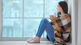 微笑的赤足妇女坐看在冬天天气的窗台 影视素材
